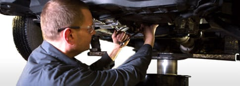 Firestone Complete Auto Care technician changing oil