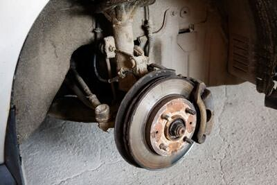 Worn brake rotor, pad, and caliper with wheel and tire removed