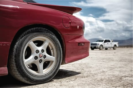 Rear tire of sports car, with pickup in the desert background